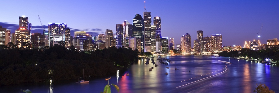 Brisbane, Queensland, Australia. City skyline during blue hour (early evening), showing reflecting lights on the river surface, rich sky and moving boat light trails.
